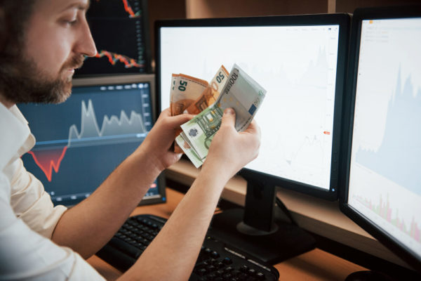 Time to get paid. Bearded man in white shirt holds earned money in the office with multiple computer screens in index charts.