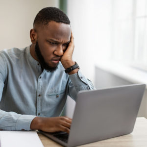 Unhappy Black Businessman Looking At Laptop Hating His Boring Job Sitting At Workplace In Modern Office. Depressed Employee, Burnout At Work. Entrepreneurship And Business Issue And Crisis Concept